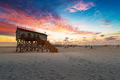 Germany, Sankt Peter Ording, pile dwellings on the beach in sunset - p300m2104131 by Markus Kapferer