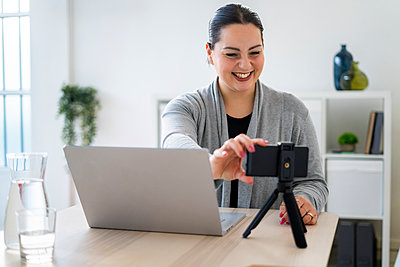 Happy businesswoman adjusting smart phone on tripod during video call at home - p300m2275326 by Giorgio Fochesato