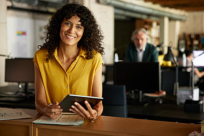 Smiling businesswoman with digital tablet leaning on table in office - p300m2299866 by Rainer Berg
