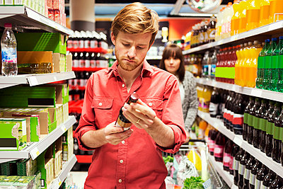 Man reading label on bottle while shopping in supermarket - p426m1017981f by Maskot