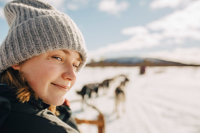 Portrait of teenage girl wearing knit hat doing dogsledding during winter - p426m2279919 by Maskot