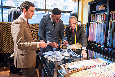 Tailors and customer choosing shirt and tie in tailors shop - p429m2004194 by G. Mazzarini