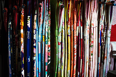 Rows of colourful fabric hanging up, traditional kimonos, a robe with wide sleeves, traditional style.  - p1100m1185704 by Mint Images