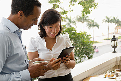 Business people using digital tablet on balcony - p555m1410017 by Roberto Westbrook