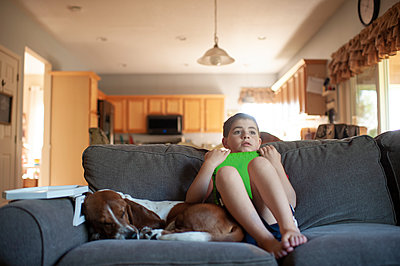 Boy relaxing next to his dog while holding his tablet on couch at home - p1166m2146857 by Cavan Images