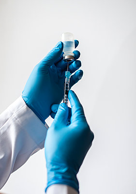 Hands in gloves drawing vaccine into syringe on white background. - p1166m2234505 by Cavan Images