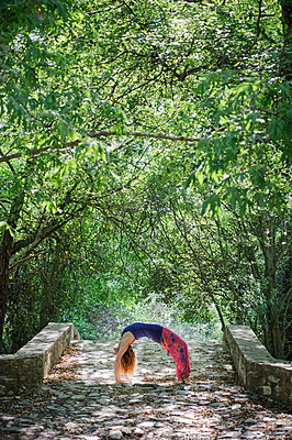 Woman in bridge yoga pose on Roudia bridge - p1580m2210137 by Andrea Christofi