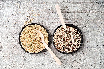 Wholemeal quinoa and popped quinoa in bowls, wooden spoons - p300m1175962 by Mandy Reschke
