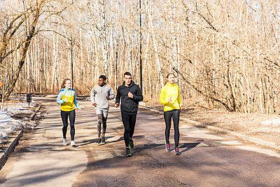 Friends running on a road in a park - p300m2005279 von William Perugini