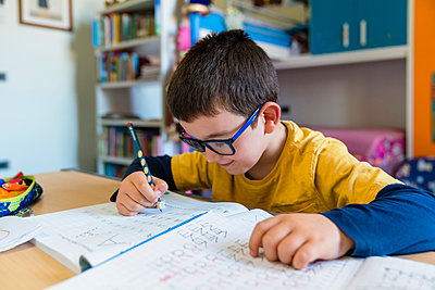 Elementary student learning while sitting at desk during homeschooling - p300m2198674 by Giorgio Magini