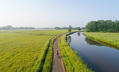 Boy cycling close to Mark river, Galder, Noord-Brabant, Netherlands - p429m2004583 by Mischa Keijser