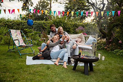 Friends taking a selfie on garden party - p788m1165286 by Lisa Krechting