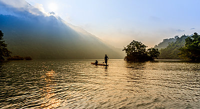 Women on a small wooden barge at sunrise, Ba Be Lake - p934m1222477 by Yan Lerval photography