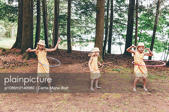 Three girls playing with Hula hoop - p1086m2149980 by Carrie Marie Burr