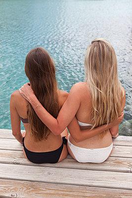 Freundinnen Arm in Arm auf Holzpier - p045m1585154 von Jasmin Sander
