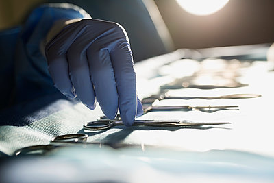Close up plastic surgeon reaching for syringe - p1192m1116621f by Hero Images