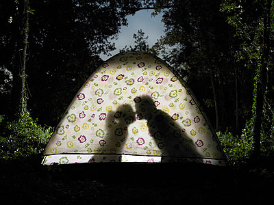 Silhouette of couple kissing in tent - p4295662 by Zac Macaulay