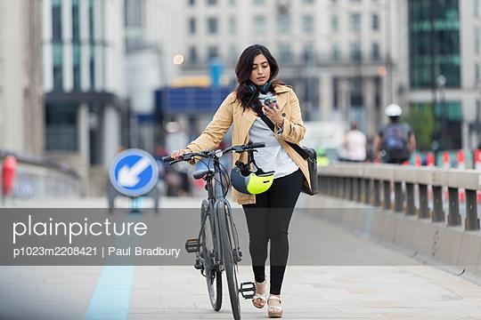 Businesswoman with smart phone walking bicycle on city bridge - p1023m2208421 by Paul Bradbury
