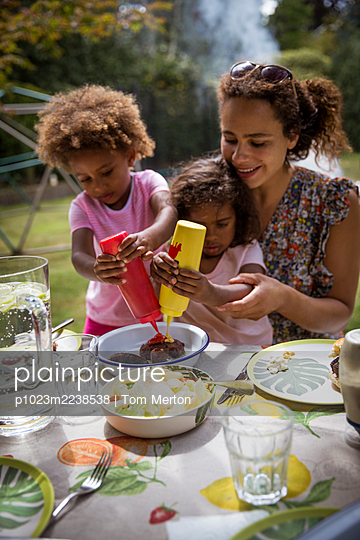 Mother and daughters enjoying summer backyard barbecue at table - p1023m2238538 by Tom Merton