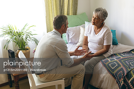 Male doctor interacting with senior female patient at retirement home - p1315m2091189 by Wavebreak
