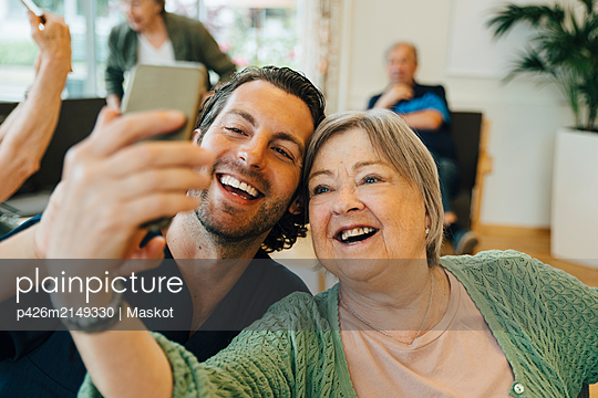Smiling senior woman taking selfie with male healthcare worker while sitting at retirement home - p426m2149330 by Maskot