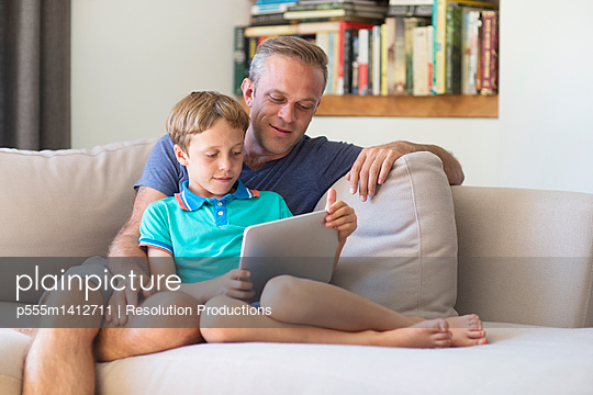 Caucasian father and son using digital tablet on sofa - p555m1412711 by Resolution Productions