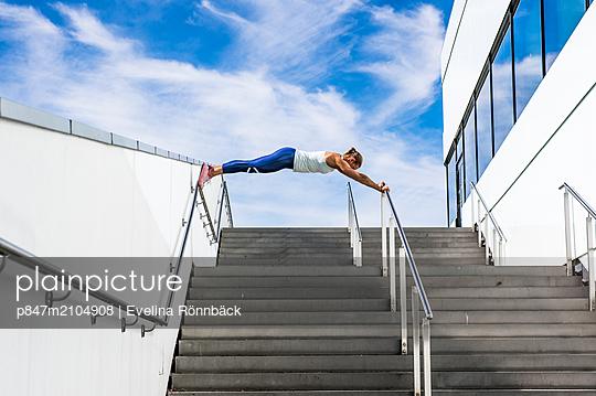 An Athletic Woman Doing Exercise On Railing Against Cloudy Sky   - p847m2104908 by Evelina Rönnbäck