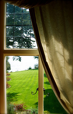 View over manicured lawns through window - p1072m829549 by Tracy Jean Shields