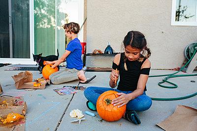 Two girls carve pumpkins outside at dusk - p1166m2078349 by Cavan Images