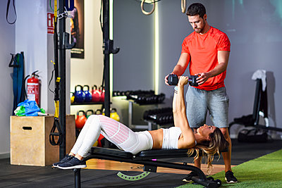 Personal trainer assisting client with weight training, lifting dumbells, lying on bench - p300m2060247 von Javier Sánchez Mingorance