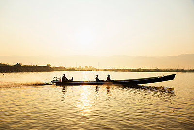 Tourists riding in canoe on rural lake - p555m1410871 by Roberto Westbrook