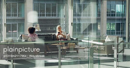 Business people sitting on sofa in modern office - p1315m2117964 by Wavebreak