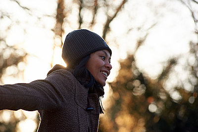 Asian woman enjoying the cold weather with wide open arms - p1166m2112880 by Cavan Images
