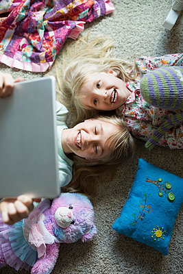 Overhead view of smiling sisters taking selfie with digital tablet - p1192m1145602 by Hero Images