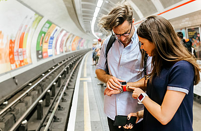 UK, London, couple waiting at   underground station platform looking at smartwatch - p300m2062095 von Marco Govel