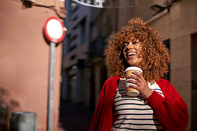 Smiling woman with disposable coffee cup looking away while standing outdoors - p300m2256713 by Veam