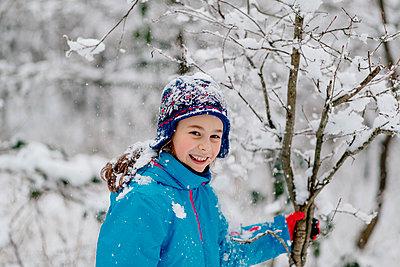 Smiling girl shaking a snowy tree - p300m2276067 by Oxana Guryanova