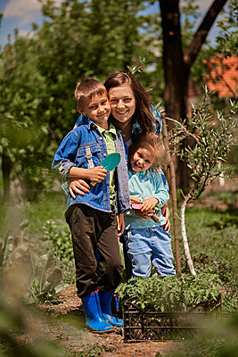 Smiling mother with son and daughter in back yard - p300m2283014 by Zeljko Dangubic