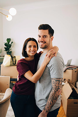 Portrait of smiling couple embracing while standing in living room during relocation - p426m1542774 by Maskot