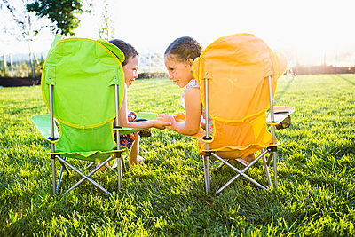 Caucasian children relaxing in lawn chairs in backyard - p555m1415636 by Mike Kemp