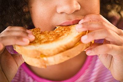 Mixed race girl eating sandwich - p555m1478120 by JGI/Jamie Grill