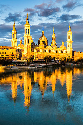 Cathedral of Our Lady of the Pillar reflected in Ebro river at sunrise. Zaragoza, Aragon, Spain - p651m2033088 by Andrea Comi
