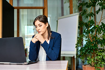 Junge Frau im Büro am Laptop - p890m1440355 von Mielek