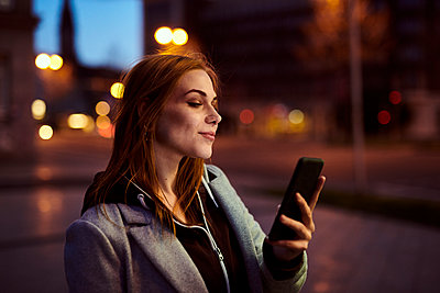 Young woman reading text message on smartphone - p890m2172107 by Mielek