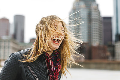 Woman with windswept blonde hair laughing, Boston, Massachusetts, USA - p924m1174850 by Lena Mirisola