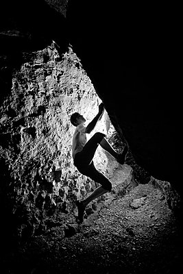 A silhouette of a climber venturing up difficult rock features inside cave in Hameln, Germany. - p1424m1501593 by Kamil Tamiola