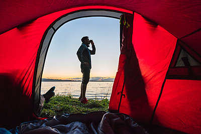 Man camping in Estonia, standing in front of tent, watching sunset - p300m2219340 by Kike Arnaiz