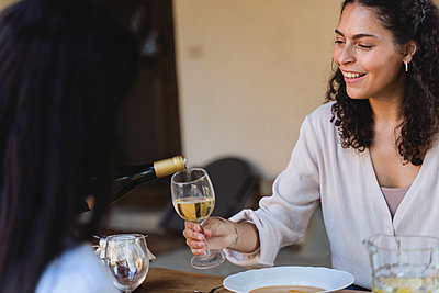 Smiling woman holding wineglass while sitting by dinning table at back yard - p300m2221095 by Francesco Morandini