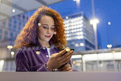 Redhead woman using smart phone at tram station - p300m2294239 by William Perugini