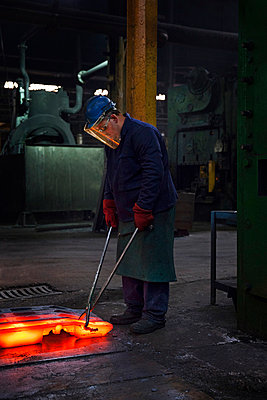 Fully forged and clipped flight bar (mining component) is lined up to cool down for final stage of finishing process - p429m875671f by Charlie Fawell